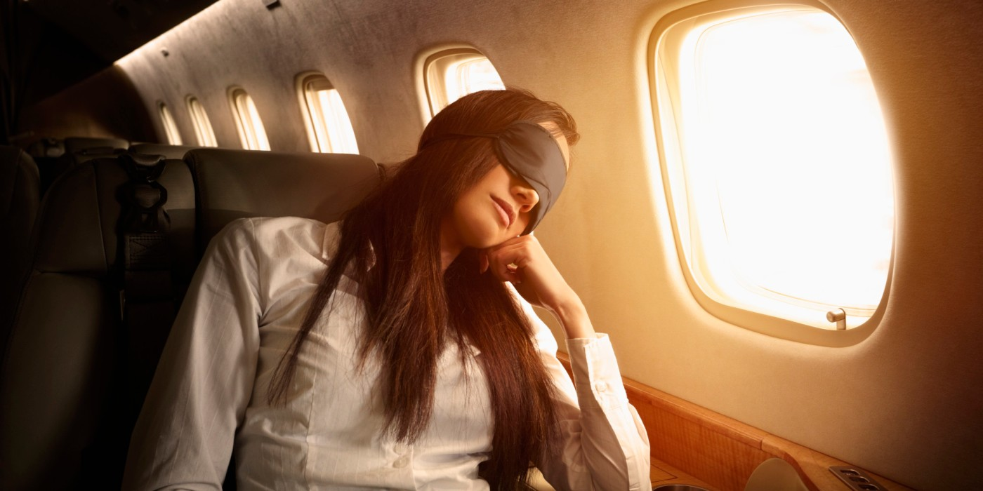 Pacific Islander businesswoman sleeping on private jet